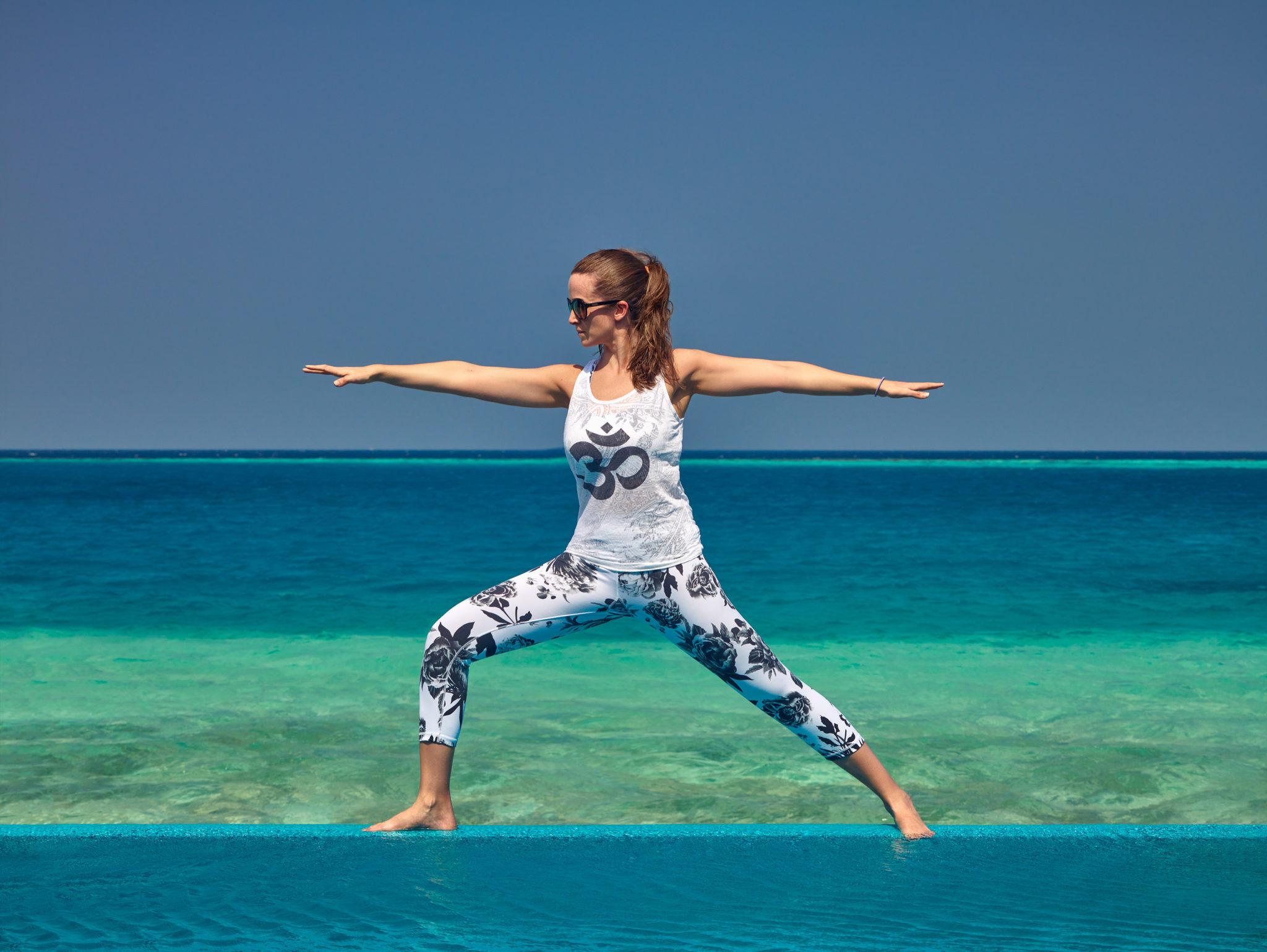 Victoria Boast Warrior Yoga Pose in front of sea