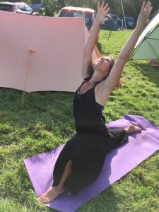 yoga between the tents at a campsite