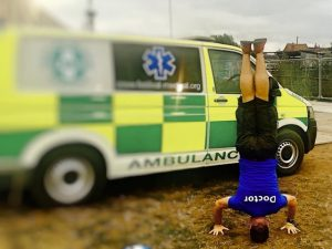 Man doing yoga in front of an ambulance
