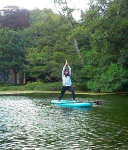 Paddleboard yoga pose on lake