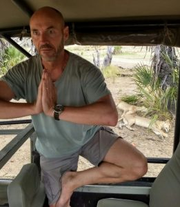 man doing Tree yoga pose in a jeep with lions behind him