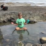 boy doing yoga in a rockpool by the sea