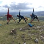 three people doing trichanasana pose on a mountain
