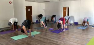 Yoga class doing forward bends