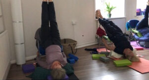 Women doing a yoga inversion on a chair in yoga studio