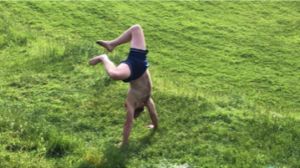 man doing a handstand in a field