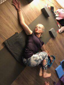 woman doing a yin yoga twist in studio