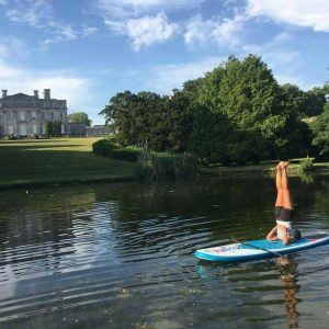 shoulderstand on a paddleboard at kingston maurward