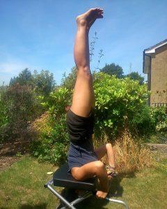 Jez doing headstand yoga pose in garden