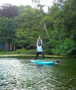Paddleboard yoga pose on lake