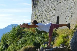 Yoga pose in front of castle in mountains